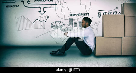 Businessman leaning on cardboard boxes against white background  against grey room - Stock Photo