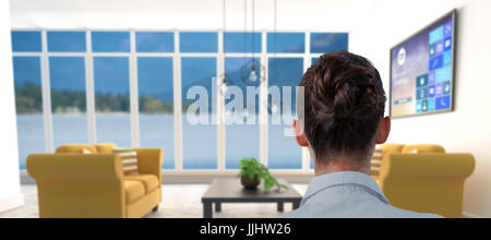 Rear view of businesswoman sitting on chair against yellow sofas on floor in modern living room - Stock Photo