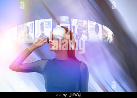 Woman wearing virtual reality glass against low angle view of glass ceiling in office - Stock Photo