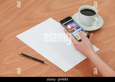 Digitally generated image of device screen against hands using mobile phone - Stock Photo