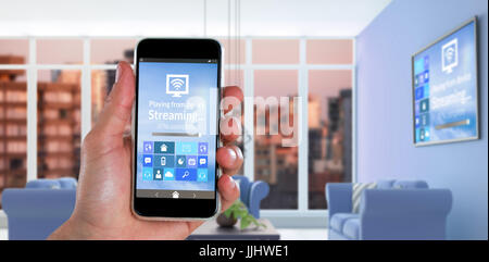 Cropped image of hand holding smart phone against digital composite interior of modern living room - Stock Photo