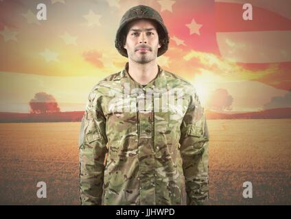 Smiling soldier standing on american flag background - Stock Photo