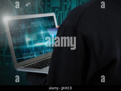 Hacker using a laptop and holding a credit card in front of digital background - Stock Photo