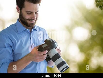 photographer looking the images on the camera. Green and white blurred lights and flares background - Stock Photo