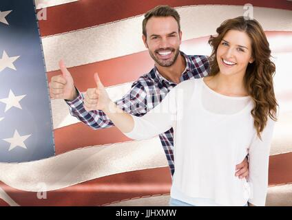 Couple thumbs up  against american flag - Stock Photo