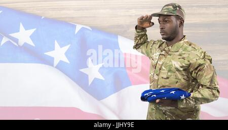 Side view of soldier holding an american flag in front of american background - Stock Photo