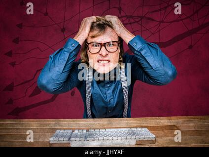 Frustrated business man at desk against maroon background and arrow graphics - Stock Photo