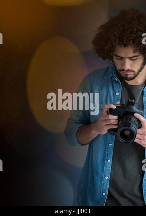 photographer looking the images on the camera. Blurred yellow  lights around him - Stock Photo