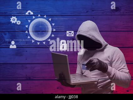 Hacker with hood holding a credit card and using a laptop in frond of wood background with digital i