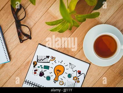 Idea doodle on notepad next to tea, glasses and plants - Stock Photo