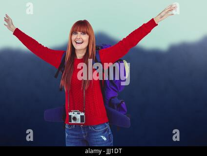 Millennial backpacker arms in air against blurry mountains - Stock Photo