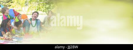 adults and children having fun celebration party with green summer copy space transition - Stock Photo