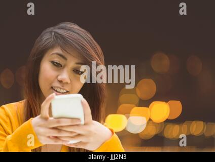 Woman Texting in night city lights bokeh - Stock Photo