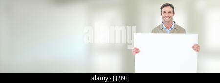 Delivery Courier holding blank card in front of blurred background - Stock Photo