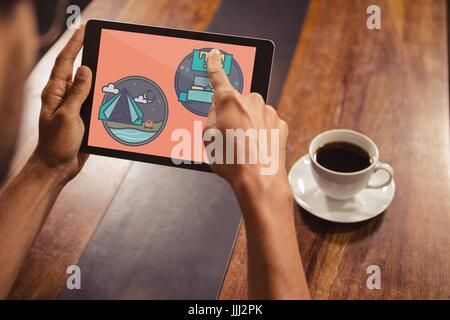 Person holding a tablet with travel icons on the screen - Stock Photo