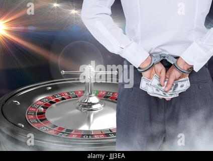 Man in hand cuffs with money and 3d roulette machine - Stock Photo