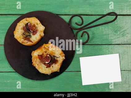 Bussiness card on green wooden desk with food and copy space - Stock Photo