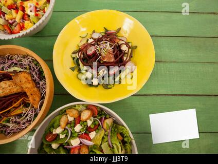 Bussiness card on green wooden desk with food and copy space on card - Stock Photo