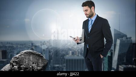 Dark sky with businessman holding phone over city - Stock Photo