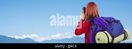 Back of millennial backpacker with camera against sky and mountain range - Stock Photo