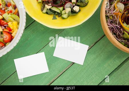 Bussiness cards on green wooden desk with food 3d - Stock Photo