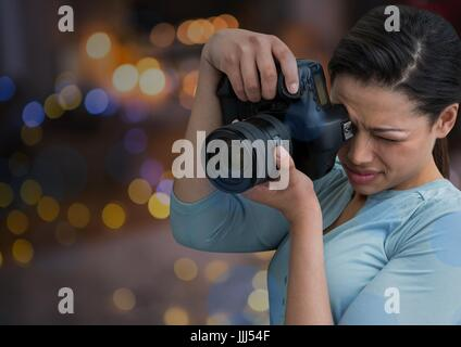 young photographer taking a photo. Blurred city lights at night behind - Stock Photo