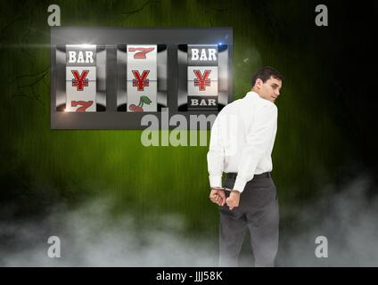 Back of Man Looking at 3d casino slot machine with hand cuffs - Stock Photo