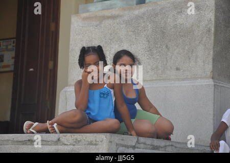 Two young local Cuban girls hang out in Havana on a hot summer afternoon - Stock Photo