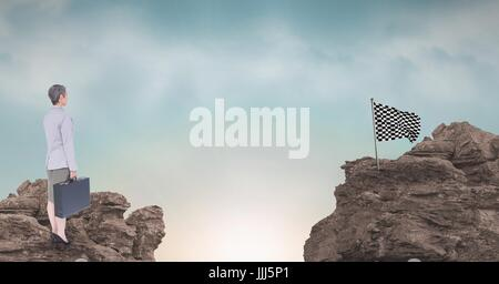 Businesswoman and checker flag on rocky mountains against sky - Stock Photo