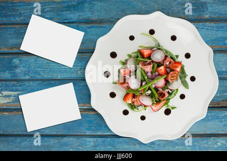 Bussiness cards on blue wooden desk with food and copy space - Stock Photo