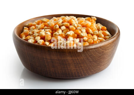 Unpopped popcorn in dark wooden bowl isolated on white. - Stock Photo