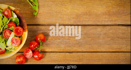 Fresh salad in bowl by tomatoes on wooden table - Stock Photo