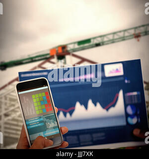 Composite 3d image of cropped image of hand holding mobile phone and graph - Stock Photo
