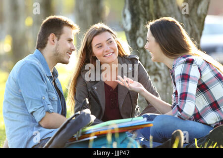 Three students talking after classes beside books and ruckpacks sitting on the grass in a park - Stock Photo
