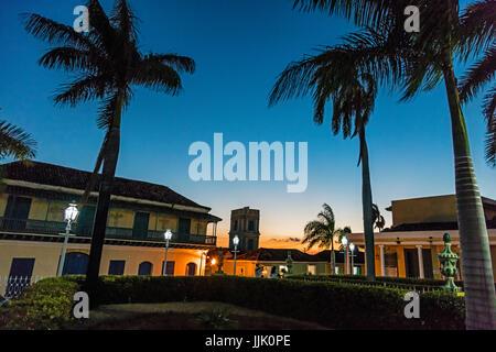 Palm trees and historic buildings on the PLAZA MAYOR at dusk - TRINIDAD, CUBA - Stock Photo