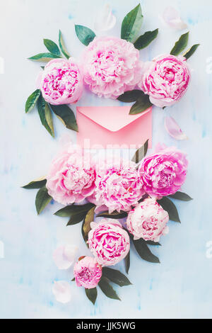 Minimal styled flat ay with peony flowers, petals and pink love letter envelope on a pastel background - Stock Photo
