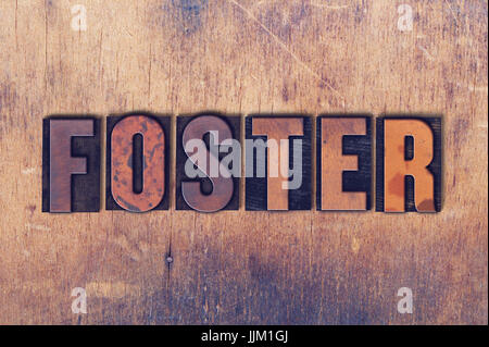 The word Foster concept and theme written in vintage wooden letterpress type on a grunge background. - Stock Photo