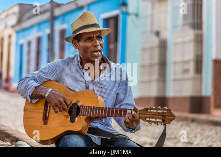 A CUBAN man plays traditional music on his guitar - TRINIDAD, CUBA - Stock Photo