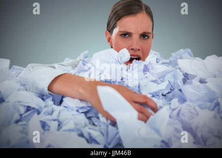 Composite image of portrait of unhappy businesswoman in heap crumpled paper - Stock Photo