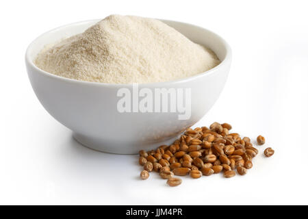 White flour  in white ceramic bowl isolated on white. Next to winter wheat kernels. - Stock Photo