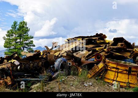 Colorful scrap metal in junk yard against a natural landscape - Stock Photo