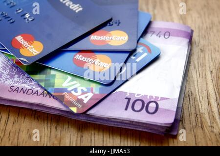 ANTIPOLO CITY, PHILIPPINES - JULY 17, 2017: A bunch of Mastercard and Visa credit cards and One hundred Philippine Peso bills on a table.