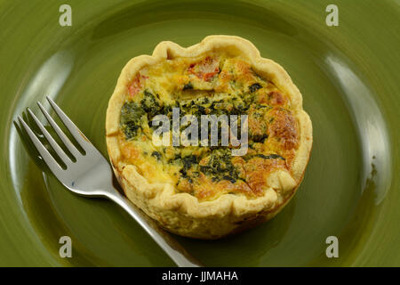 Individual portion quiche florentine with spinach, feta cheese and tomato in green plate - Stock Photo