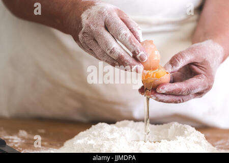 Senior woman adding egg to pastry. Focus on broken egg and old working hands. Horizontal orientation, saturated - Stock Photo