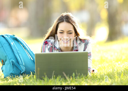 Front view of a happy student watching on line content in a laptop lying on the grass of a park - Stock Photo