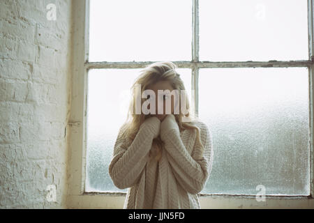 Scared young woman wearing a wool jumper standing by the window looking away - Stock Photo