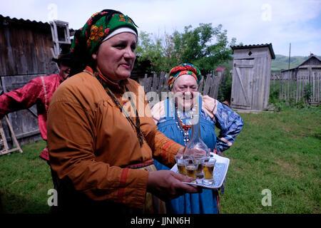 Elderly Russian women wearing traditional sarafan dress serving homemade homemade Samogon distilled alcoholic beverage - Stock Photo