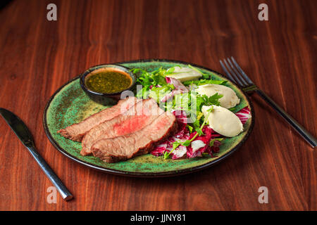 Sliced grilled beef steak with green leaves salad on rustic plate with cutlery. Medium rare barbecue steak and healthy - Stock Photo