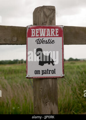 a beware dog patrol sign on wooden fence; Essex; UK - Stock Photo
