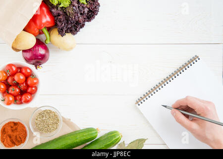 Close-up partial view of person holding pencil and writing recipe in cookbook while cooking - Stock Photo